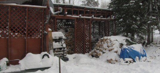 Our woodshed, the splitter covered with a tarp until spring