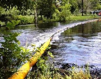 A boom is deployed on the Kalamazoo River in July 2010.  It doesn't seem to be containing or deflecting much dilbit.  InsideClimateNews-Rebecca West photo 22Oct2014.