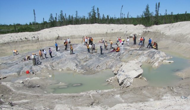 On July 14 this year, participants in a Mineral Exploration Forum examine the exposure of the F Zone of the old MacLeod-Cockshutt mine.  Note the overburden heaped up around the site.  Photo by E.J. Lavoie.
