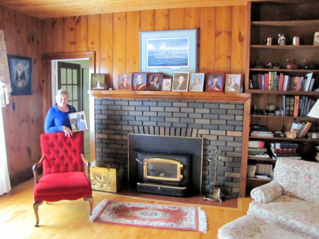 Eileen Pile poses in front of the fireplace in her heritage home at MacLeod Townsite, surrounded by pictures of family.