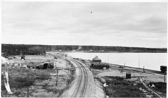 Longlac Station, junction of Nakina Cut-off, post 1925. View looking east. No highway yet bordering the lake & no overpass. Line in foreground to Nakina. Line near lake to Jellicoe. Longlac Historical Society collection.