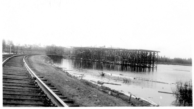 View looking east towards Longlac in 1941. An overhead (i.e., bridge) is under construction to pass over the Kenogami River and railway trestle to accommodate the new highway. Photo courtesy of Greenstone Historical Society.