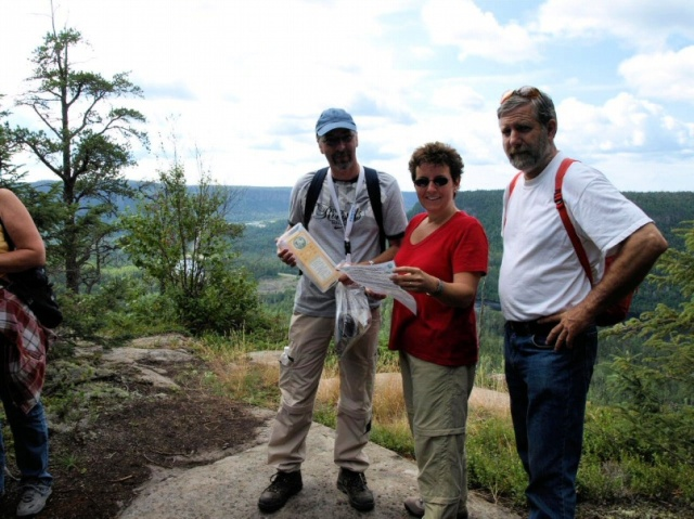 Two visitors from overseas (left) examine a geocache at one of the overlooks. L to R, Paul Kathmann, Mary Kathmann, and Peter Kathmann.